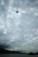 A plane flies below the cloudy sky of BC's Sunshine Coast, Canada (albatz) Tags: sky clouds mountains plane cloudy bc sunshinecoast canada
