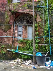 Worn Brick Wall in Rangoon with Scaffolding and Garbage Can