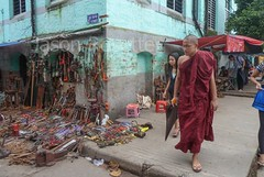 Monk Walks Past Tools for Sale on Sidewalk and Wall in Downtown Rangoon, Burma