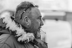 Keeping warm (Frank Fullard) Tags: frankfullard fullard candid street portrait warm cold weather fur wool glasses smoker black white blanc noir monochrome fair carbootsale carboot castlebar mayo face expression beard irish ireland coat jacket collar fleece snug
