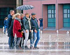 It Rains on All Sides (Hindrik S) Tags: rain umbrella fountain water regenschirm people mensen minsken peuple leute gens rein regen nat wet wiet mouillées nas nass wasser wetter streetphoto strjitfotografy strasenfotografie straatfotografie girls boys candid zaailand wilhelminaplein saailân liwwadden ljouwert leeuwarden 19 2019 on1photoraw2019 on1pics tamron tamronaf16300mmf3563dillvcpzdmacrob016 16300 sonyphotographing sony sonyalpha sonya77ii sonyilca77m2 slta77ii α77 a77ii