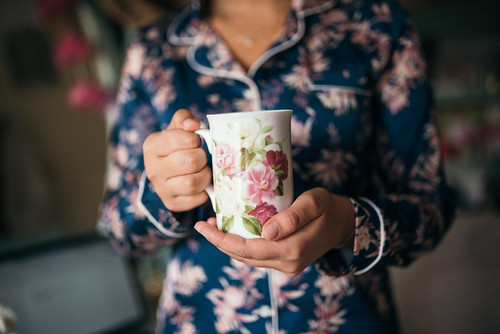 Girl in flower pajamas holding flower cup for good morning. Girl drinking tea.