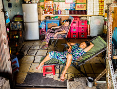 Asleep in Saigon heat (Phg Voyager) Tags: saigon vietnam girls asleep sleeping shop color leica mp phgvoyager chairs dirty beer indoor asia urban streetphotography photography summilux 24mm city citylife old poor fan nap