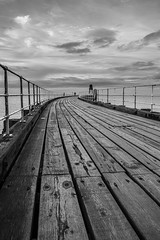 Whitby Pier Mono (Christopher Combe Photography) Tags: monochrome pier planks whitby grain water sea ocean yorkshire england coast curve boardwalk wood lighthouse