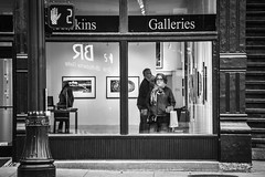 Inside Looking Out (tim.perdue) Tags: short north arts district columbus ohio downtown urban city high street nikon d5600 nikkor 18140mm candid black white bw monochrome mono blackandwhite man woman person figure inside looking out gallery window reflection shop storefront sidewalk crosswalk light sign stare expression art painting hammond harkins galleries door stairs steps walk hand 2