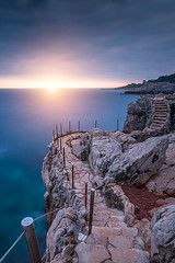 Stairway to sunset ... ( Cap d'Antibes - France ) (Yannick Lefevre) Tags: europe france frenchriviera cotedazur capdantibes chemindescontrebandiers sunset longexposure seascape landscape cliff sun clouds way path sea blue sky mediterraneansea