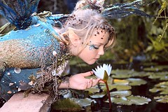 Tending to the Lilies (wyojones) Tags: texas texasrenaissancefestival toddmission faire renaissance renfest fest festival fairy waterfairy blonde cute pretty lovely beautiful beauty girl teen wings seashells facepaint lipstick redlips starfish costume lips eyes blueeyes makeup waterlilies bloom smell ears water andrea usa