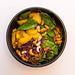 Indian Summer Bowl Top view mit Blattspinat, Zuckerschoten, warme Rosmarin Kartoffeln, Rohkostsalat, geröstete gelbe Karotten, Cashews, Basilikum, Koriander sowie gelbe Thai-Curry Sauce