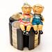Rentnerpaar auf gestapelten Münzen vor weißem Hintergrund - Altersvorsorge