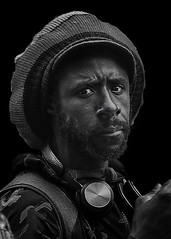 Portrait (D80_546934) (Itzick) Tags: candid copenhagen bw blackbackground bwportrait beard hat blackman face facialexpression streetphotography earphones portrait d800 itzick