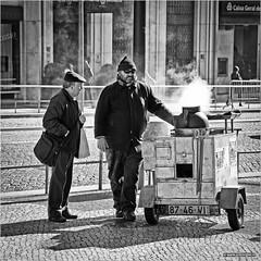 Chestnuts in Lisbon (John Riper) Tags: portugal lisboa street johnriper bw white black monochrome canon john square photography mono zwartwit candid 6d 24105 straatfotografie riper people sun man glasses stand pavement mosaic lisbon stall chestnuts l seller smoke steam cap