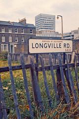 Longville Road (AntyDiluvian) Tags: england greatbritain britain london vintage 1973 hotel londonparkhotel elephantandcastle streetsign longvilleroad southwark fence roughhewn vacantlot