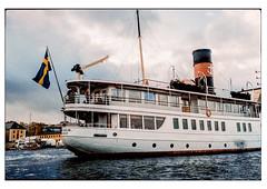 (schlomo jawotnik) Tags: 2019 oktober stockholm schweden holm fahne flagge schiff schornstein passagiere rettungsring kran beiboot bullauge gebäude ufer analog film kodak kodakproimage100 usw