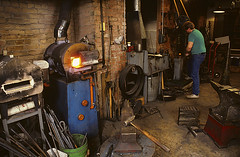 Blacksmith working preparing metal to be put back in furnace (Jim Corwin's PhotoStream) Tags: blacksmith iron hot redhot artisanship fire forge forging fuel glowing goldsmith indoors metal metalworker metalworking precision production make making visualarts closeupview danger tradition traditional furnace heat business industry workshop flame flames artandcraft metalobjects metalwork photography horizontal job manuallabor metalindustry laborer occupation tools shop equipment male men steel craft realpeople concentration smallbusiness anvil hammer