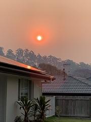 Smoky Sunset. (marsh_maureen) Tags: sun sunset smoke reflection houses roofs glow