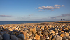 Opposite end of the day (music_man800) Tags: cley beach shingle stones sea north coast coastline shore sunny sun blue sky evening light lighting shadow autumn autumnal golden hour afternoon october people walk walking outside outdoors nature natural glow pebbles rock landscape scene scenery norfolk uk united kingdom canon 700d adobe lightroom creative cloud edit photography clouds arty artistic focus blur background