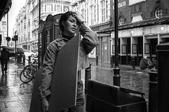 The Poster (markfly1) Tags: london soho england uk street photography candid image woman walking holding poster board hand gesture mono blackandwhite monochrome baw bw asian sad forlorn weary look theatre thatreland cobbled road bicycle heavy rain wet pavement