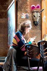 Passing the Time (esallen52) Tags: portrait woman indoors cafe phone decor daytime seated chairs