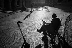 A quiet November morning (Roberto Spagnoli) Tags: controluce monopattino scooter biancoenero blackandwhite bw backlight verona italy people lightsandshadows fotografiadistrada streetphotography reading newspaper alone