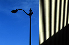 Silhouetted lamp post in front of building on a sunny afternoon downtown Seattle Washington State USA (Jim Corwin's PhotoStream) Tags: downtown building lamppost silhouetted design shapes cityscape urbanscene architecture city streetlight nobody outdoors buildingexterior photography horizontal contrast lightanddark line lines bluesky seattle