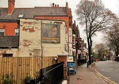 Connie's Nine Mile Caribbean Takeaway (Andrew 62) Tags: conniesninemilecaribbeantakeaway evingtonroad highfields leicester street dereliction trees bobmarley fence wall bin shoppingtrolley shops buildings road
