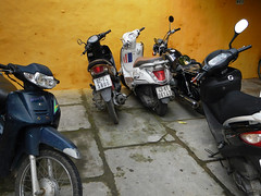 Motorcycles parked against a yellow wall in Hoi An, Vietnam (albatz) Tags: yellow wall motorcycles parked hoian vietnam