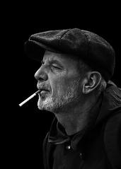 Portrait (D80_547254) (Itzick) Tags: bw candid copenhagen cigarette streetphotography smoking hat man bwportrait beard blackbackground portrait face facialexpression denmark d800 itzick