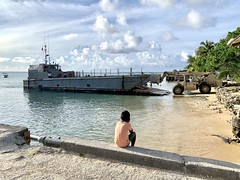 A Marshall Islander watches Seabees offload materials and tools on Kwajalein Atoll in the Republic of the Marshall Islands.
