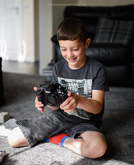 Nikon D200 unboxing (Steven Robinson Pictures) Tags: nikond810 present boy cute portrait indoors toy play fun smiling birthday camera 50mmf18dnikkor browneyes holding sitting carpet domesticlife learning photography learningphotography teaching