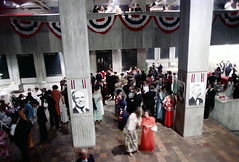 74-269 (ndpa / s. lundeen, archivist) Tags: nick dewolf nickdewolf color photographbynickdewolf 1975 1970s film 35mm 74 reel74 autumn fall boston massachusetts cityhall governmentcenter party gala event people crowd decorations banners men women mayorwhite kevinwhite photo photograph balcony concrete brutalist brutalism architecture interior lobby pillar post patrioticdecorations tuxedo tuxedos bowtie blacktie formal