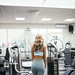 Young woman in sportswear going to do sports training, gymnastics. Indoors gym.