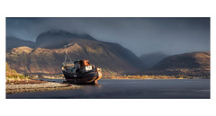 Done Fishing (panorama) (Dave Fieldhouse Photography) Tags: scotland corpach boat trawler wreck stranded beach fortwilliam highlands bennevis loch water mountains mountain houses town light sunset clouds mood autumn fuji fujifilm fujixt2 stitchedpanorama panorama wide landscape landscapephotography wwwdavefieldhousephotographycom roadtrip