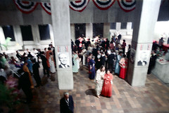 74-268 (ndpa / s. lundeen, archivist) Tags: nick dewolf nickdewolf color photographbynickdewolf 1975 1970s film 35mm 74 reel74 autumn fall boston massachusetts cityhall governmentcenter party gala event people crowd decorations banners men women mayorwhite kevinwhite photo photograph balcony concrete brutalist brutalism architecture interior lobby pillar post patrioticdecorations blurry outoffocus tuxedo tuxedos bowtie blacktie formal