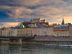 Salzburg on a winter evening (echumachenco) Tags: salzburg city architecture history medieval baroque sky vivid cloud evening sunset river water salzach building fortress festung castle hohensalzburg spire austria österreich canonpowershotg12 winter february snow
