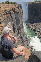 Victoria Falls Gorge (peterkelly) Tags: digital canon 6d africa intrepidtravel capetowntovicfalls zimbabwe victoriafalls zambeziriver gorge canyon cliff waterfall water man hat sitting edge rock rocky basalt