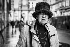 Fluffy Hat (Leanne Boulton) Tags: urban street candid portrait portraiture streetphotography candidstreetphotography candidportrait streetportrait eyecontact candideyecontact streetlife old elderly woman female lady face eyes expression mood emotion feeling necklace chains fur furry fluffy hat cold weather style fashion tone texture detail depthoffield bokeh naturallight outdoor light shade city scene human life living humanity society culture lifestyle people canon canon5dmkiii 70mm ef2470mmf28liiusm black white blackwhite bw mono blackandwhite monochrome glasgow scotland uk
