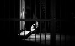 behind bars (Sven Hein) Tags: frau menschen zigarette leute strasse nacht herbst schwarzweiss strassenfotografie behindbars woman people cigarette eyecontact street streetlife night autumn fall bw blackandwhite candid streetphotography olympus penf