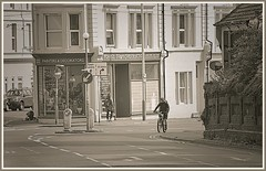 Coming round the corner. (tony allan tony allan) Tags: cyclist sepia mono monochrome architecture street streetphotography streetlife nikond5300