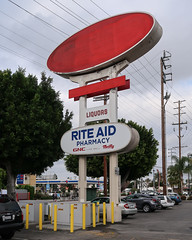 Red jewel for Rite Aid Hard Liquor drugstore on Santa Monica Boulevard. (Tim Kiser) Tags: nonsign bollards roadsidesign ellipse losangelescalifornia electricpoles parking staplessign losangeles riteaidpharmacy 1970sign paintedoversign parkedcars padmountedtransformers la paintedover california numerousbollards liquorstore southerncalifornia riteaidliquor electriclines parkinglot april2019 redellipse 1970 transformerboxes telephonepoles formerstaples ellipticalsign april staples vacantbusiness redpaint powerlines formerstaplesstore easthollywood emptysign yellowbollards 20190421 img9013 gnc overcast pharmacy blanksign drugstore riteaidliquorstore riteaidsign manybollards thriftyicecream 1970s overheadelectriclines formerus66 1970ssign riteaid us66 paintstreaks utilitypoles losangelescountycalifornia santamonicaboulevard 2019 overheadpowerlines liquors txtchg