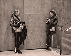 Candid of Two Young Ladies in MoMA (nrhodesphotos(the_eye_of_the_moment)) Tags: dsc005033001084 wwwflickrcomphotostheeyeofthemoment theyeofthemoment21gmailcom moma candid patrons texture blackandwhite women casual stair interior monochrome reflections shadows nyc manhattan galleries texting relaxing stairs metal glass space museum tile