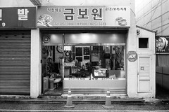 Shop (OzGFK) Tags: 35mm asia chm100 ei400 korea ricoh ricoh35zf analog blackandwhite film monochrome pushedtwostops urban pushedfilm southkorea bw streetphotography gwangju wet rain aftertherain streetshop retail