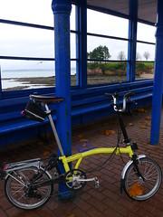 Yellow and Blue (cycle.nut66) Tags: brompton bike bicycle cycle yellow m type 6 speed folder folding torquay devon panasonic lumix lx5 leica summicron blue shelter coast seaside out season cold rainy day