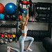Attractive fit female doing lunge fitness exercise with blue kettlebell weight.