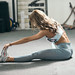 Fit woman  stretching her leg in gym