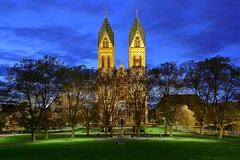 Scheinidylle (ploh1) Tags: freiburg herzjesukirche blauestunde langzeitbelichtung nachtaufnahme kirchtürme himmel park architektur hisorischesbauwerk bäume herbst