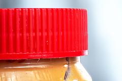 Peanut Butter Lid (Ian Charleton) Tags: macromondays lids jar container lid food kichen red texture