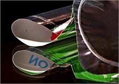 One's hers, one's mine! (jesse1dog) Tags: yoghurt lid foil pot writing aluminum metal shiney curves rolled green reflections mirror russianindustar61lz industar2850mmlens lumixgm1 bokeh vintageprime tabletop macromondays lids