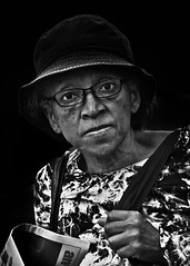 Portrait (D80_543684) (Itzick) Tags: candid copenhagen bw blackbackground bwportrait woman hat glasess face facialexpression streetphotography newpaper portrait denmark d800 itzick