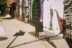 Is that man praying? (colinpoe) Tags: 6x9 manhattan mediumformat streetphotography grafitti shadows street signage cinestill lowereastside nyc fujicag690 rangefinder gothamist cinestill50 newyorkcity les 120 fujica