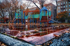 A trip down memory lane, when I was a kid I would love to play in the rain. (The park was all mine...) (cesar.toribio1218) Tags: aftertherain playground reflection red empty pointofview photography wet rainy reflections perspective newyorkcitystreets newyork